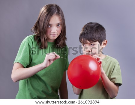 Popping brother's balloon. - stock photo