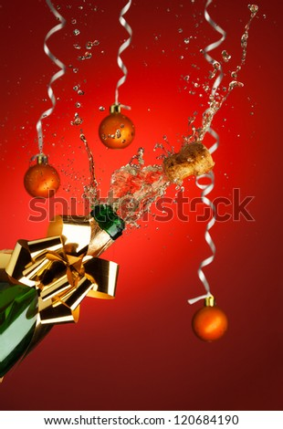 Popping cork from Champaign bottle with Christmas balls on background - stock photo