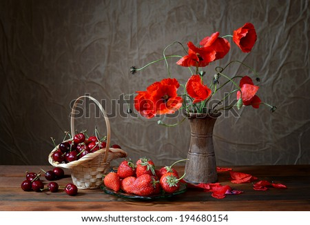 Poppy in a ceramic vase, cherries and strawberries on table - stock photo