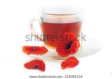 Poppy in glass cup on white table  - stock photo