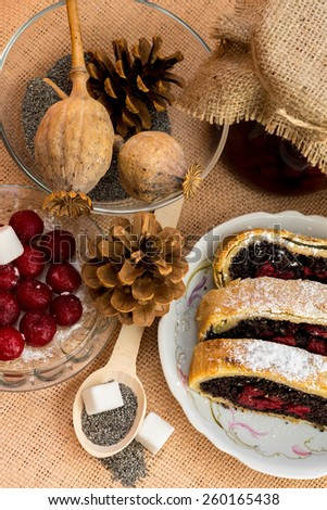 Poppy seed strudel with cherry on the sacking - stock photo