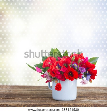 Poppy, sweet pea and corn flowers in por on table   isolated on white background - stock photo
