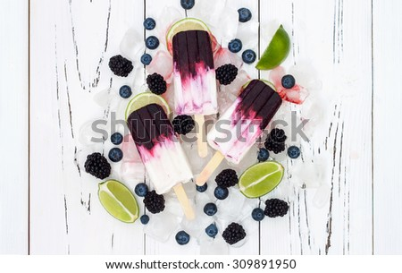 Popsicle with yogurt, blueberries, blackberries and lime - stock photo