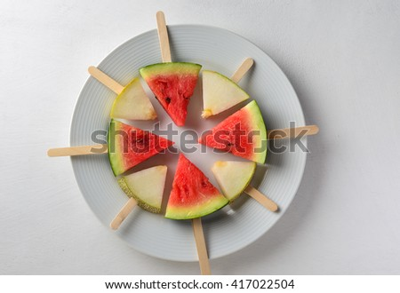 Popsicles of sweet melon and watermelon. Healthy and fun substitute to sugary food for kids. - stock photo