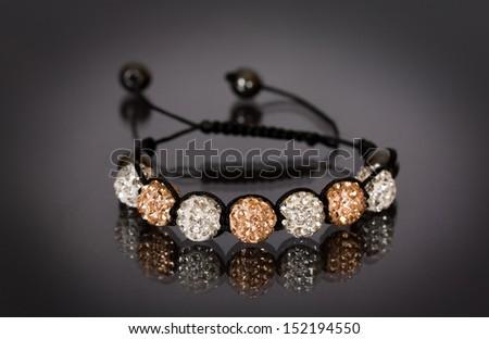 Popular Buddhist bracelet shamballa on a black background - stock photo
