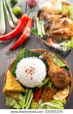 Popular delicious Indonesian local food nasi ayam penyet, indonesian fried chicken rice with sambal belacan. Fresh hot with steam smoke. - stock photo