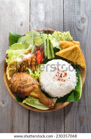 Popular Indonesian local food nasi ayam penyet, indonesian fried chicken rice with sambal belacan. Fresh hot with steam smoke. - stock photo