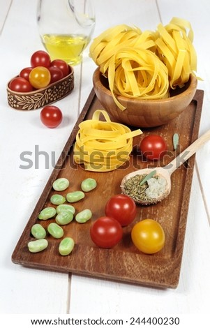 Popular Ingredients Italian cuisine: pasta, beans, tomatoes and olive oil on a wooden tray.  Focus selective - stock photo