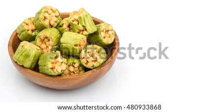 Popular Japanese snack small pieces of sweet, deep fried flour with brown sugar (karinto), wrapped with thick matcha skin in wooden bowl over white background