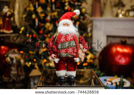 Porcelain Christmas toys in the form of Santa Claus with gift bag on the glittering indoors background