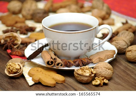Porcelain coffee cup on the table. Garnish with star anise, cinnamon, nuts, gingerbread. Christmas time. - stock photo