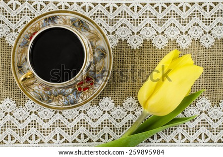 Porcelain coffee cup with yellow flower on linen background - stock photo
