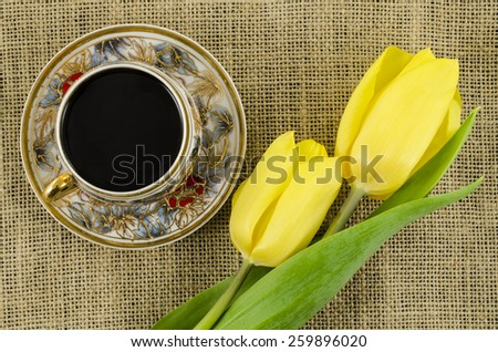 Porcelain coffee cup with yellow flowers on linen background - stock photo
