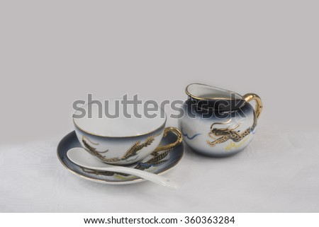 Porcelain cup and milk jug. White and blue porcelain Chinese. Gold blue dragons. - stock photo