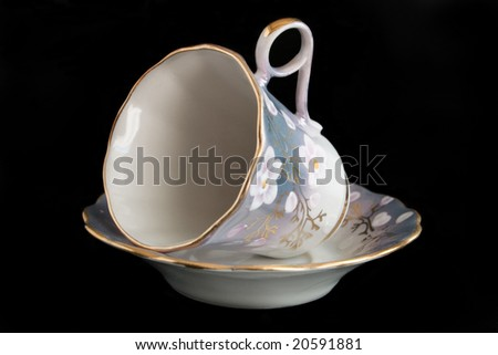 porcelain cup and saucer on a black background