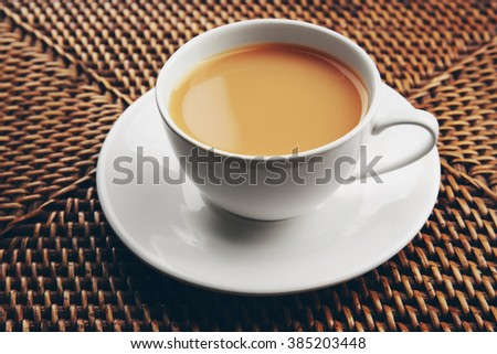 Porcelain cup of tea with milk on wicker background - stock photo