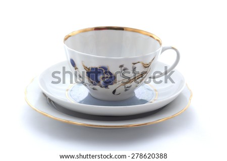 Porcelain cup, saucer and plate on white - stock photo