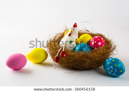 Porcelain Hen in a nest with painted Easter eggs on a white background. Close up. Easter background. Easter background. Easter symbol. Copy space - stock photo