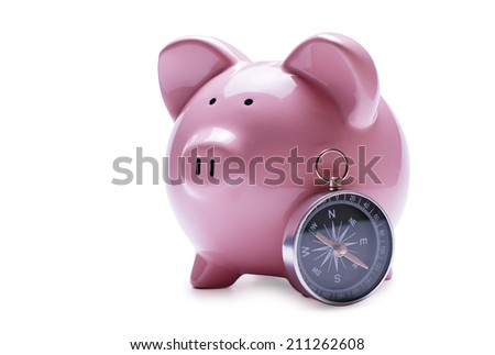 Porcelain pink piggy bank next to a vintage compass, concept of savings and guidance, close-up with shadow on white