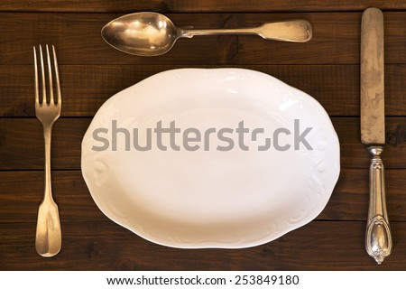 Porcelain plate and the vintage cutlery on a wooden table - stock photo