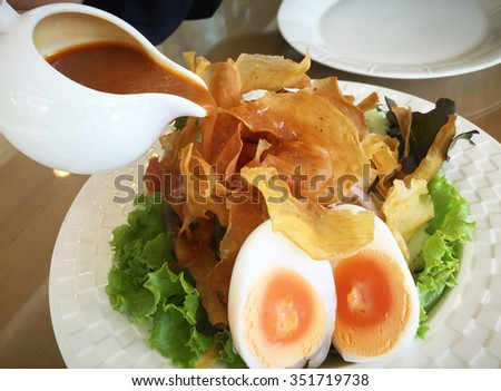 Poring curry dressing sauce into Fresh salad with crispy potato and boiled eggs - stock photo