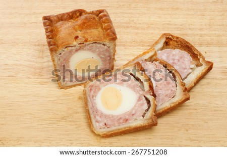 Pork and egg pie with cut slices on a wooden board - stock photo