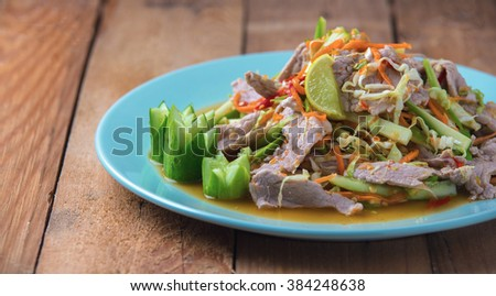 Pork and vegetable spicy salad with lemon. The Thai food on plate