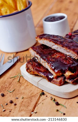 Pork barbecue ribs with sauce and french fries on a vintage wooden table - stock photo