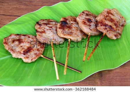 pork barbeque. Marinated pork skewers. grilled pork in banana leaf plate on wood table. pork steak. Asian barbecue. Thai food street. Traditional Thai roasted pork. bbq. - stock photo