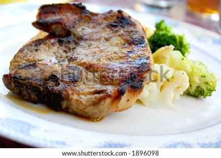 Pork chip dinner with steamed vegetables - stock photo