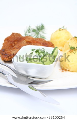 Pork chop (covered in batter and breadcrumbs), mashed potatoes and cucumber salad in a bowl decorated with dill on a plate with a fork and a knife on white background