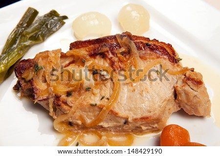 pork chop dish with vegetables, leeks, carrots and onions. pork meat cooked - stock photo