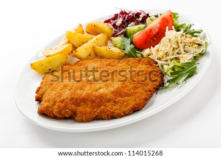 Pork chop, roasted potatoes and vegetables - stock photo