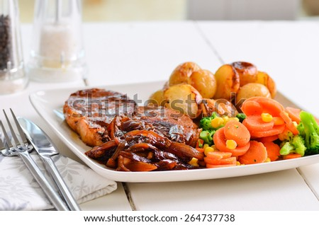 Pork chop Sunday lunch with onion gravy. - stock photo