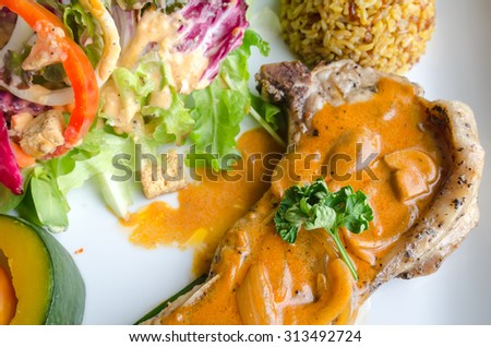 Pork Chop with mushroom mustard sauce, brown rice, salad and steamed pumpkin on white ceramic dish - stock photo