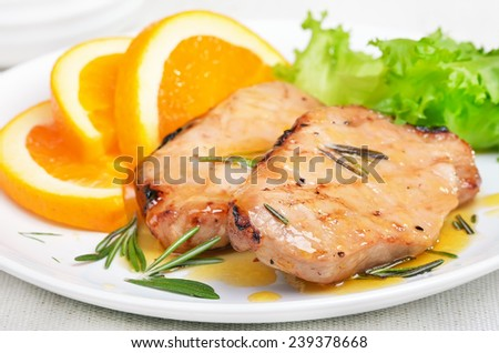 Pork chop with orange sauce and rosemary, close up view - stock photo