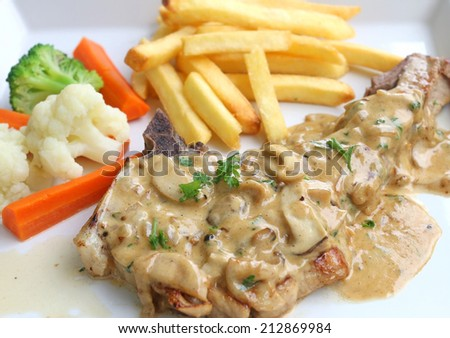 Pork chop with potato fried, vegetable and mushroom sauce