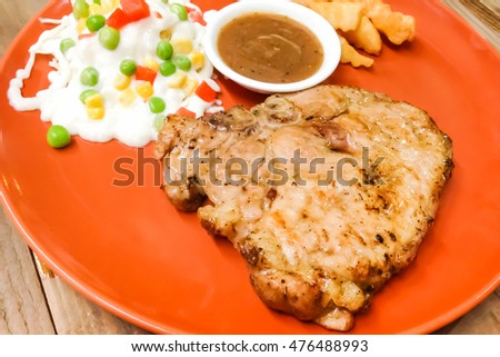 Pork chop with sauce and salad on a plate, Grilled Pork chop prepare for serve to customer on the table.