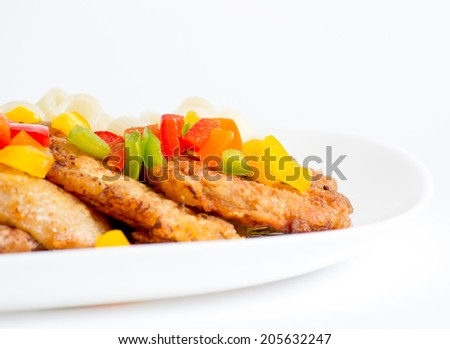 Pork chop with sweet pepper and pasta on white plate