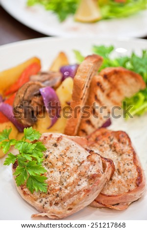 Pork chop with vegetable at plate - stock photo
