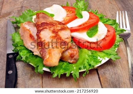 pork chops and salad caprese  - stock photo