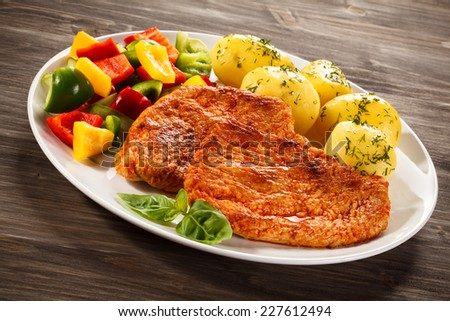 Pork chops, boiled potatoes and vegetables