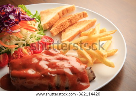 Pork chops spicy sauce on white dish and wooden background