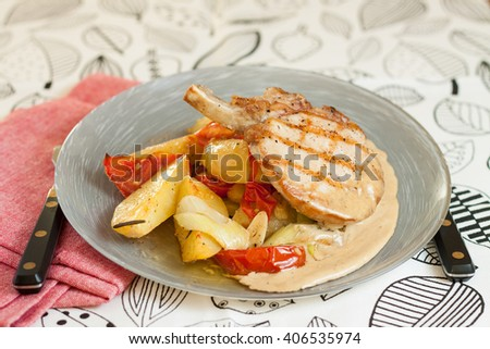 Pork chops with grilled potatoes, tomatoes, leeks and rosemary served with spicy mustard sauce - stock photo