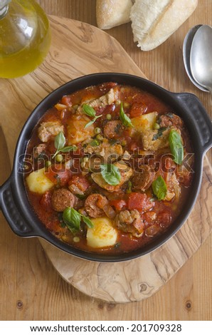 Pork, chorizo and pea stew topped with basil - stock photo