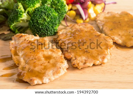 Pork cube steak topped with pepper sauce and creamy salad on wood plate - stock photo