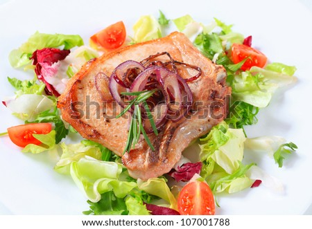 Pork cutlet on nest of green salad