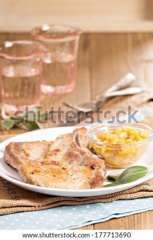 Pork cutlets on a bone with apple and raisin chutney - stock photo