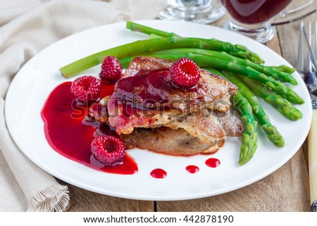 Pork cutlets with raspberry sauce and asparagus on white plate, horizontal - stock photo