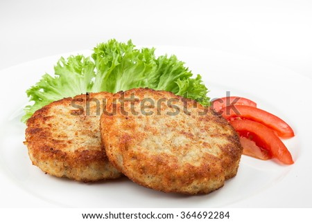 Pork cutlets with salad and slices of tomato isolated on white background - stock photo